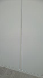 Detalle de armario de puertas abatibles, lacado en blanco, Tirador fresado en V
